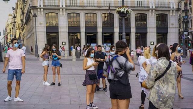Người đi bộ đeo khẩu trang trên đường phố Madrid (Tây Ban Nha). Ảnh: Bloomberg