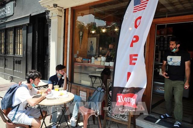 Người dân thưởng thức bữa ăn tại một nhà hàng ở New York, Mỹ, sau khi lệnh mở cửa trở lại bước vào giai đoạn mới. Ảnh: THX/TTXVN