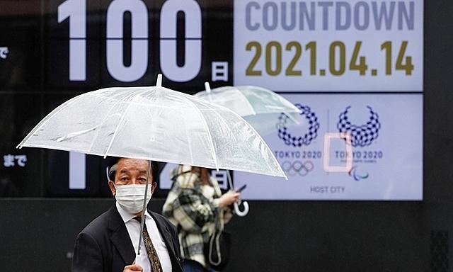 Người dân Nhật Bản đi qua tấm bảng đếm ngược ngày khai mạc Olympic Tokyo hôm 14/4. Ảnh: Reuters