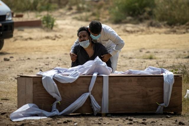 Người thân ngồi trước quan tài bệnh nhân tử vong vì Covid-19 ở New Delhi. Ảnh: Reuters.