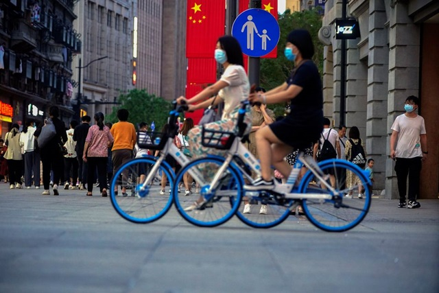 Woman ride bikes on a street, following the outbreak of the coronavirus disease (COVID-19), in Shanghai, China May 10, 2021. REUTERS/Aly Song
