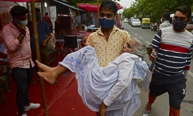 Người thân đưa bệnh nhân Covid-19 bị khó thở đến trung tâm hỗ trợ oxy miễn phí ở ngoại ô New Delhi, Ấn Độ hôm 10/5. Ảnh: AFP.