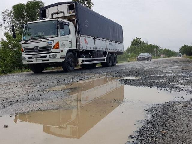 Quốc lộ 62 thường xuyên xuống cấp, đọng nước gây nguy hiểm cho các xe. Ảnh: Kiên Định