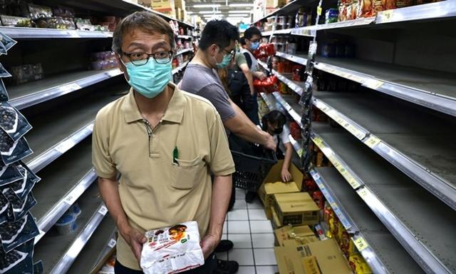 Người dân Đài Loan vét sạch các kệ đựng hàng tại một siêu thị hôm 15/5. Ảnh: Reuters.