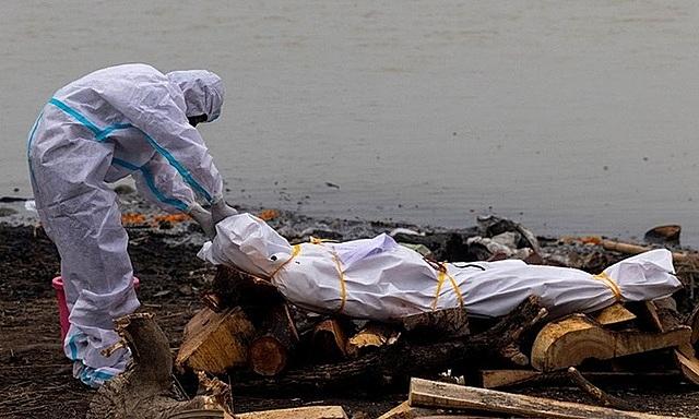 Người đàn ông mặc đồ bảo hộ chạm vào thi thể của người thân chết vì Covid-19 trước khi hỏa táng trên bờ sông Hằng tại bang Uttar Pradesh, Ấn Độ, hôm 6/5. Ảnh: Reuters.