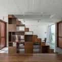 <p> Ngoài cùng là không gian sinh hoạt chung, được chia làm 2 phần, ngăn cách nhau bằng một cầu thang gỗ ở giữa. Một bên là bếp, một bên là phòng khách. Hai lớp cửa đối diện nhau cũng được thiết kế thoáng khí, giúp không gian trở nên thông thoáng.</p>