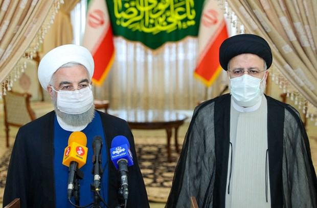 Tổng thống sắp mãn nhiệm Iran Hassan Rouhani (trái) gửi lời chúc mừng Tổng thống đắc cử Ebrahim Raisi (phải) trong cuộc họp báo ở Tehran ngày 19/6/2021. (Ảnh: AFP/TTXVN)