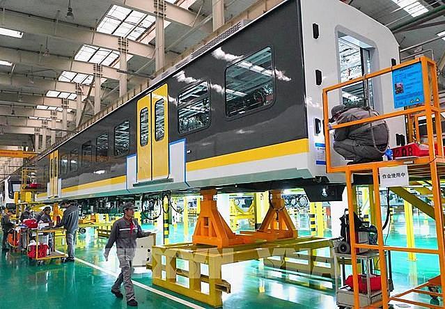 Công nhân làm việc bên trong một dây chuyền sản xuất ở Đường Sơn, tỉnh Hà Bắc, Trung Quốc. Ảnh: THX/ TTXVN