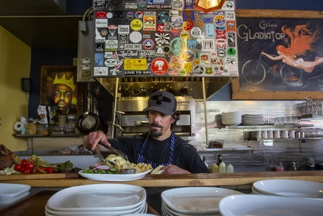 Because Forage is short of workers, it is cutting lunchtime service and asking staffers to work overtime. Chef Andrew Grasso, above, plates a meal.