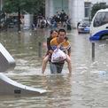 """<p class=""""Normal""""> Ít nhất 25 người đã thiệt mạng và nhiều khu vực rộng lớn ở tỉnh Hà Nam, miền trung Trung Quốc, chìm trong nước ngày 21/7, theo nhà chức trách địa phương. Một số chuyên gia nói đợt mưa vừa qua tại khu vực là """"lớn nhất 1.000 năm"""".</p> <p class=""""Normal""""> Một người đàn ông đưa một phụ nữ qua đoạn đường lụt do mưa lớn ở thành phố Trịnh Châu, thủ phủ tỉnh Hà Nam, ngày 21/7. Ảnh: <em>Reuters</em>.</p>"""