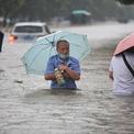 """<p class=""""Normal""""> Người dân Trịnh Châu đi qua một tuyến đường ngập nước ngày 20/7. Ảnh: <em>Reuters</em>.</p>"""