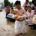 """<p> Một người đàn ông ôm con lội qua con đường ngập nước sau trận mưa lịch sử """"1.000 năm có một"""" ở Trịnh Châu, tỉnh Hà Nam, Trung Quốc vào ngày 22/7. Hàng chục nghìn người phải sơ tán khỏi các vùng bị lũ lụt ở miền trung Trung Quốc. Từ ngày 17/7 đến 20/7, lượng mưa tại Trịnh Châu là 61 cm, gần tương đương với mức trung bình hàng năm là 63,5 cm. Ảnh: <em>Reuters</em>.</p>"""