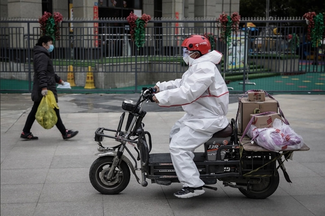 """Shipper trở thành """"phao cứu sinh"""" của phần lớn người dân Vũ Hán trong thời gian phong tỏa. Ảnh: NPR."""
