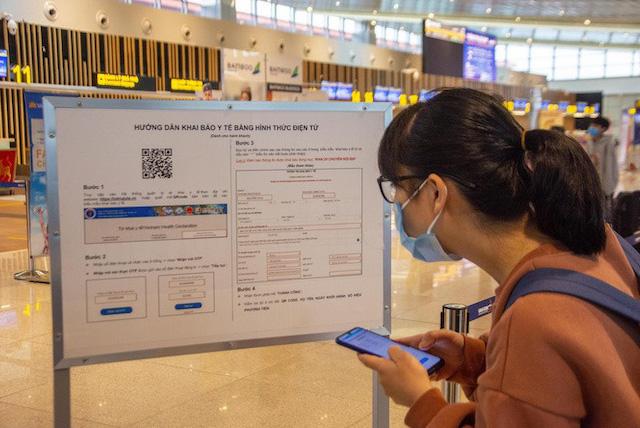 Hành khách xem hướng dẫn khai báo y tế tại sân bay Vân Đồn. Ảnh: Người Lao Động.