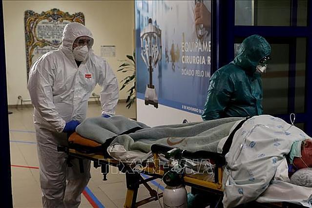 Nhân viên y tế chuyển bệnh nhân nhiễm COVID-19 tới bệnh viện ở Lisbon, Bồ Đào Nha. Ảnh: THX/TTXVN