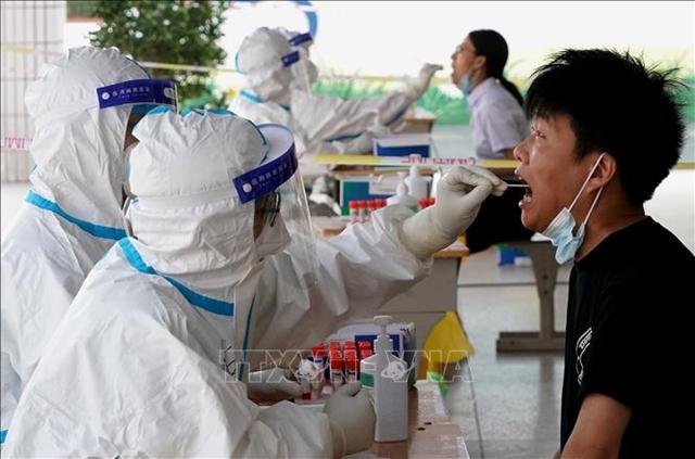 Nhân viên y tế lấy mẫu xét nghiệm Covid-19 cho người dân tại Trịnh Châu, tỉnh Hà Nam, Trung Quốc, ngày 4/8. Ảnh: THX/TTXVN