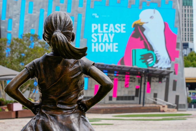"""The Fearless Girl Statue looks at a """"Please Stay Home"""" sign in an empty Federation Square on the first day of a five-day lockdown implemented in the state of Victoria in response to the coronavirus disease (COVID-19) outbreak in Melbourne, Australia, February 13, 2021. REUTERS/Sandra Sanders/Files/File Photo"""