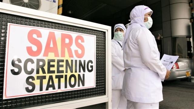 Nhân viên y tế xét nghiệm SARS cho những người lái xe ô tô tại cửa khẩu biên giới giữa Singapore và Malaysia năm 2003. Ảnh: Reuters