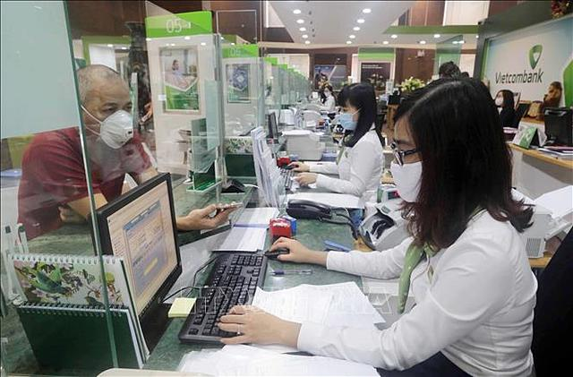 Áp lực xử lý nợ xấu: Cần hành lang pháp lý mạnh hơn - Ảnh 1.  Khách hàng giao dịch tại Hội sở chính Vietcombank, Hà Nội. (Ảnh minh họa: Trần Việt/TTXVN).