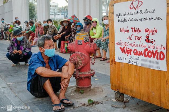 Những người dân có hoàn cảnh khó khăn ngồi chờ nhận quà từ một nhóm từ thiện trên đường Lý Chính Thắng (quận 3, TP HCM) chiều 3/4.