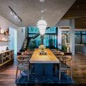 <p> Để ngôi nhà hòa nhập với không gian xung quanh, kiến trúc sư đã cải tạo thiết kế từ 2,5 tầng thành 2 tầng, đồng thời giữ nguyên công năng gồm 3 phòng ngủ, phòng khách, bếp ăn, phòng sinh hoạt ... Kiến trúc sư cũng đào sâu móng nhà để tăng chiều cao tầng 1 lên 5,4 m, sau đó xây thêm tầng lửng.</p>
