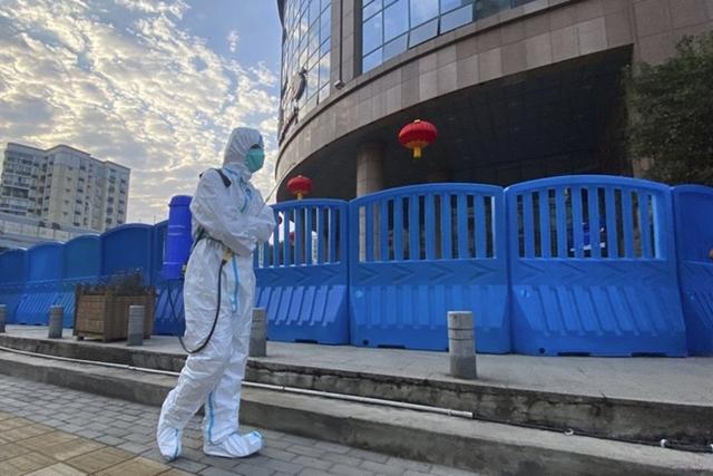 Một công nhân mang theo thiết bị khử trùng đi dạo bên ngoài Bệnh viện Trung ương Vũ Hán, Trung Quốc vào tháng 2. Ảnh: AP.