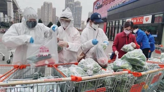 Tình nguyện viên hỗ trợ phân loại và đóng gói hàng tạp hóa ở một siêu thị tại Vũ Hán. Ảnh: Reuters
