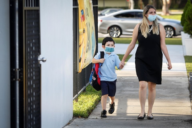 A teacher walks with a student, as they wear protective masks on the first day of school, amid the coronavirus disease (COVID-19) pandemic, at St. Lawrence Catholic School in North Miami Beach, Florida, U.S. August 18, 2021. REUTERS/Marco Bello