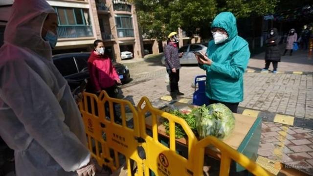 Một người dân sử dụng điện thoại thanh toán các loại rau được mua thông qua đơn đặt hàng theo nhóm ở Vũ Hán ngày 21/2/2020. Ảnh: Reuters
