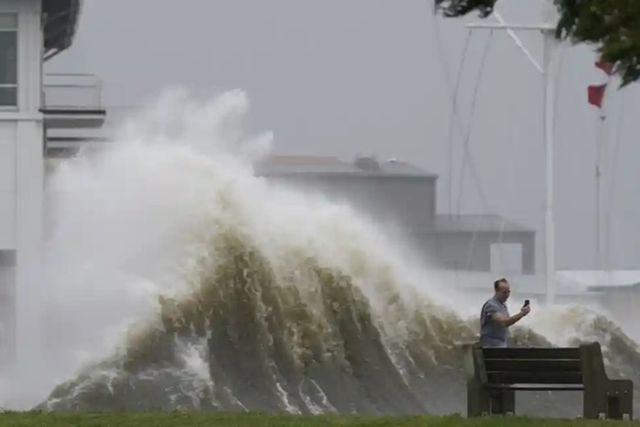 Một người chụp ảnh sóng lên cao dọc bờ hồ Pontchartrain tại New Orleans. Ảnh: AP.