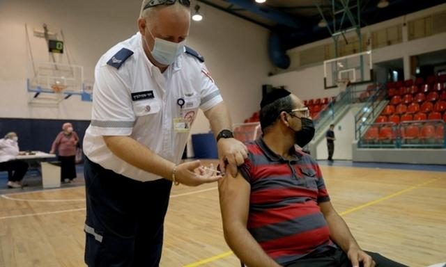 Một nhân viên y tế tiêm mũi vaccine Covid-19 tăng cường của Pfizer cho người dân tại điểm tiêm chủng ở Holon, Israel, hôm 24/8. Ảnh: AFP.