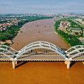 <p> Cầu Đông Trù bắc qua sông Đuống, nối liền quận Long Biên và huyện Đông Anh, giúp giải tỏa ùn ứ giao thông liên tỉnh từ hướng Hải Phòng, Quảng Ninh đi các tỉnh Tây và Tây Bắc Hà Nội. Cầu gồm 3 nhịp cầu đôi, bề rộng mặt cầu 54,5 m, ứng dụng công nghệ vòm ống thép nhồi bê tông, lần đầu tiên được áp dụng tại Việt Nam. Công trình có khả năng chịu được động đất cấp 8. <em>Ảnh: Hoàng Hà</em></p>