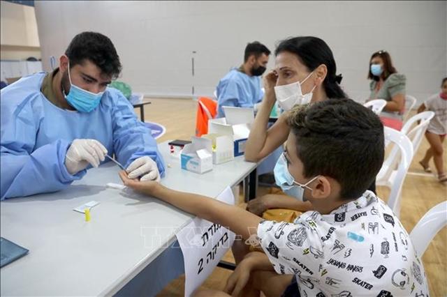 Nhân viên y tế lấy mẫu xét nghiệm kháng thế đối với Covid-19 cho học sinh tiểu học trước ngày khai trường tại Rishon LeZion, Israel ngày 22/8. Ảnh: THX/TTXVN