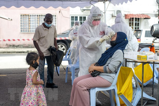 Nhân viên y tế lấy mẫu xét nghiệm Covid-19 cho người dân tại Selangor, Malaysia ngày 14/8. Ảnh: THX/TTXVN.