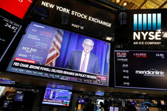 A screen displays the Federal Reserve Chair Jerome Powell on the trading floor at New York Stock Exchange, July 28, 2021. REUTERS/Andrew Kelly
