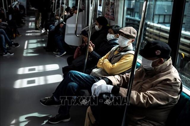 Người dân đeo khẩu trang để phòng chống dịch Covid-19 trên phương tiện công cộng tại Tokyo, Nhật Bản. Ảnh: TTXVN