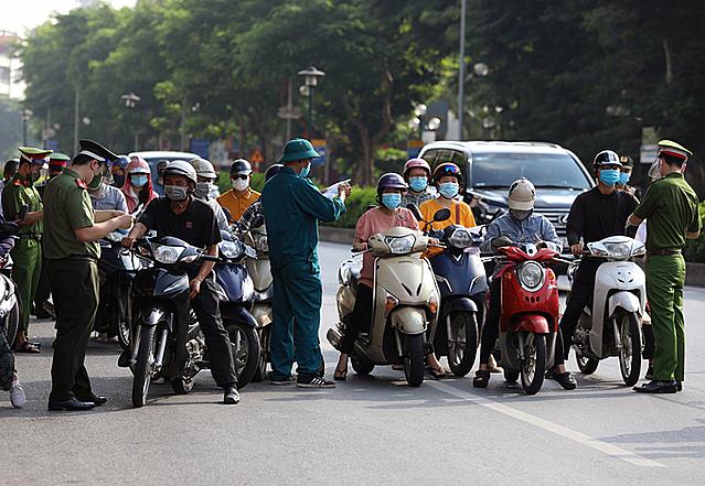 Lực lượng chức năng kiểm tra giấy đi đường của người tham gia giao thông tại chốt kiểm soát đầu cầu Chương Dương sáng 4/9. Ảnh: Ngọc Thành.