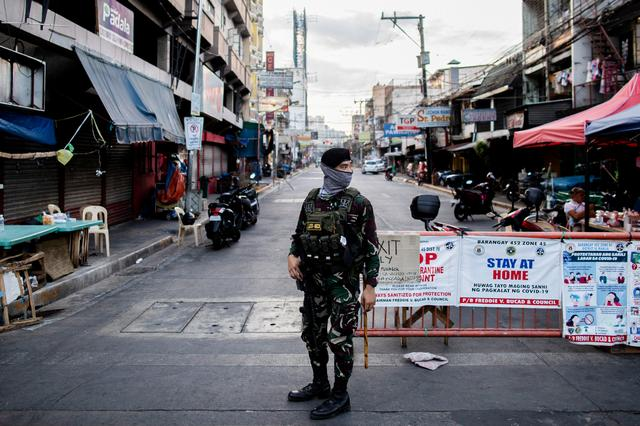 FILE PHOTO: A soldier wearing a face mask holds on his weapon as he guards an empty street following the lockdown imposed to contain the coronavirus disease (COVID-19) in Manila, Philippines, April 24, 2020. REUTERS/Eloisa Lopez