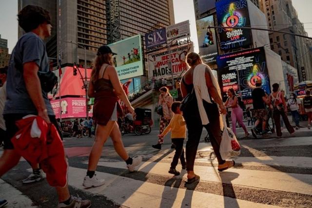 Người đi bộ băng qua đường tại New York ngày 4/9. Ảnh: Bloomberg.