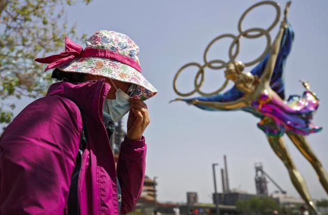 Một phụ nữ điều chỉnh khẩu trang khi đi ngang qua bức tượng trượt băng nghệ thuật Thế vận hội Mùa đông Bắc Kinh được trưng bày tại Công viên Shougang ở Bắc Kinh ngày 2/5. Ảnh: AP.