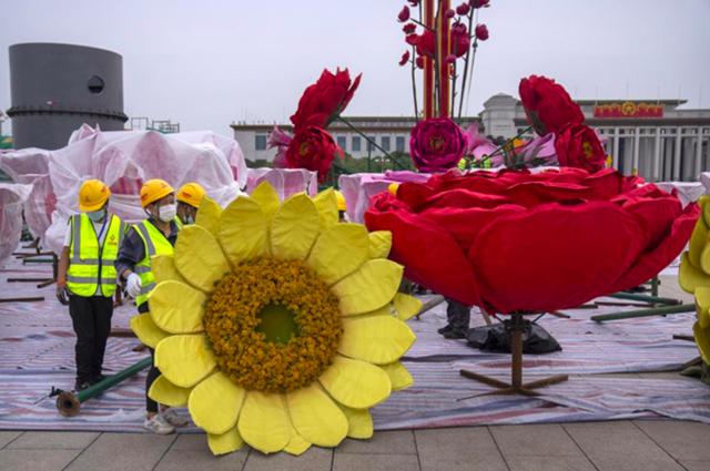 Các công nhân di chuyển một bông hoa khổng lồ để chuẩn bị cho kỳ nghỉ Quốc khánh của Trung Quốc trên Quảng trường Thiên An Môn ở Bắc Kinh ngày 18/9. Ảnh: AP.