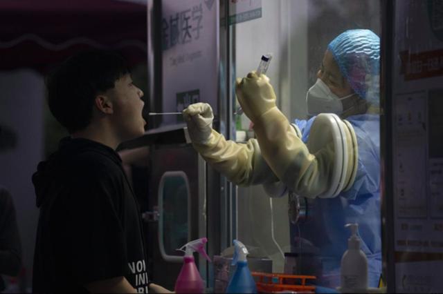Một người đàn ông được nhân viên y tế lấy mẫu xét nghiệm Covid-19 ở Bắc Kinh vào ngày 18/9. Ảnh: AP.