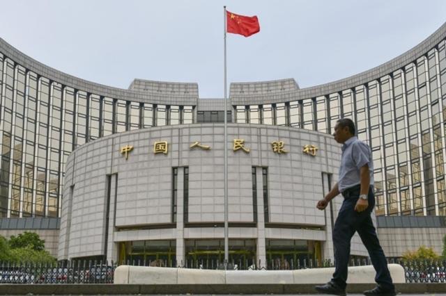 Người dân đi ngang qua trụ sở Ngân hàng Nhân dân Trung Quốc ở Bắc Kinh. Ảnh: ChinaDaily.