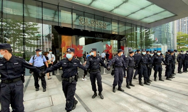 Security personnel form a human chain outside Evergrande's headquarters in Shenzhen, where people gathered this month to demand repayment of loans and financial products © David Kirton/Reuters