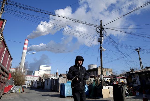 FILE PHOTO: A man walks near a coal-fired power plant in Harbin, Heilongjiang province, China, November 27, 2019. REUTERS/Jason Lee/File Photo